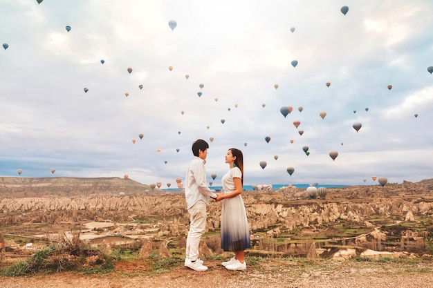 Asian couple watching colorful hot air balloons flying over the valley at cappadocia, turkey