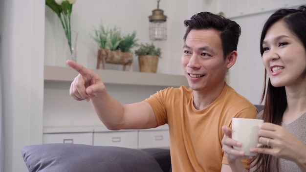アジアのカップルがテレビを見ていると自宅の居間で暖かいコーヒーを飲む、甘いカップル