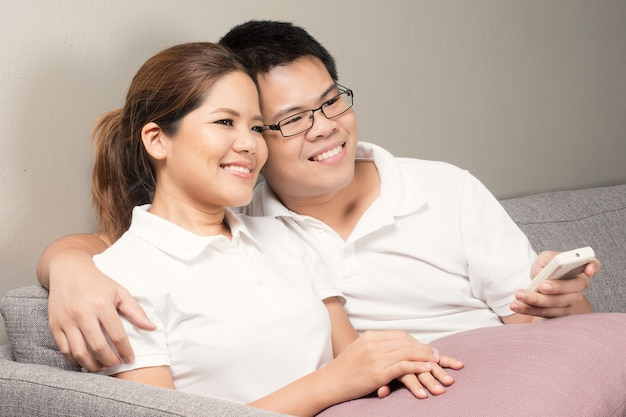 家でテレビを見ているアジアのカップル