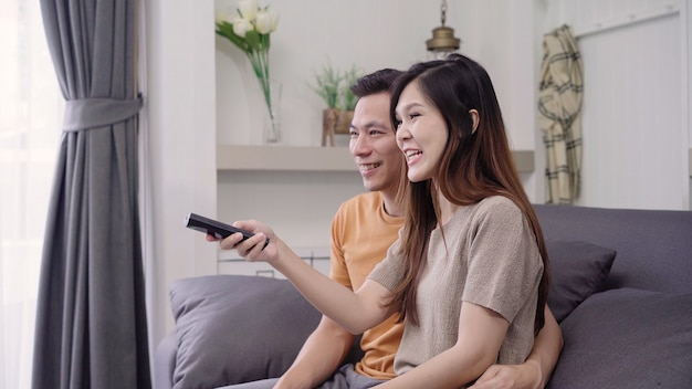 Asian couple watching tv and drinking warm cup of coffee in living room at home, sweet couple enjoy