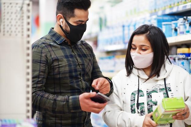 Азиатская пара носит защитную маску, делая покупки вместе в супермаркете во время пандемии. покупка через интернет со смартфона - лучший выбор.