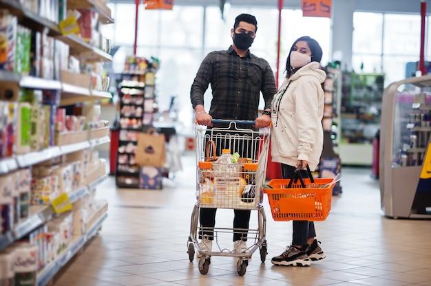 アジアのカップルは、パンデミック時にスーパーマーケットで一緒に買い物をする保護フェイスマスクを着用します。