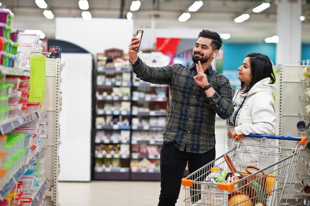 アジアのカップルはスーパーマーケットで一緒に買い物をし、電話で自分撮りをします。