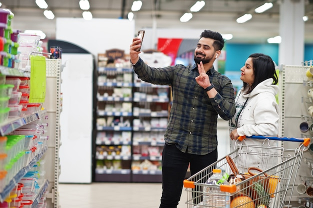 Asian couple wear shopping together in supermarket, making selfie by phone.