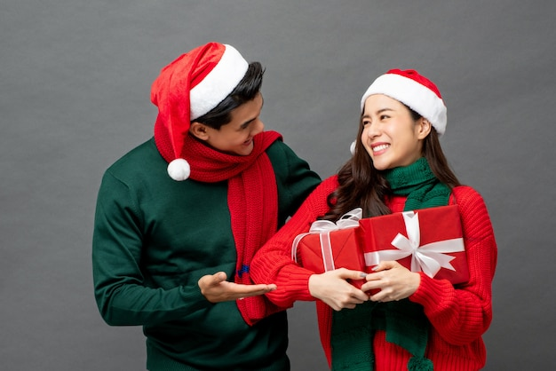 Asian couple wearing colorful red and green sweaters with christmas gift boxes