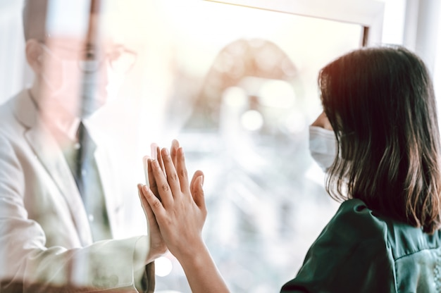 Asian couple wearing face mask separated because of the quarantine