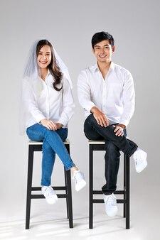 흰색 셔츠와 청바지를 입고 아시아 커플 의자에 앉아 웨딩 베일을 입고 여자