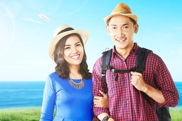 모자와 배낭을 메고 바다가 보이는 들판을 여행하는 아시아 커플