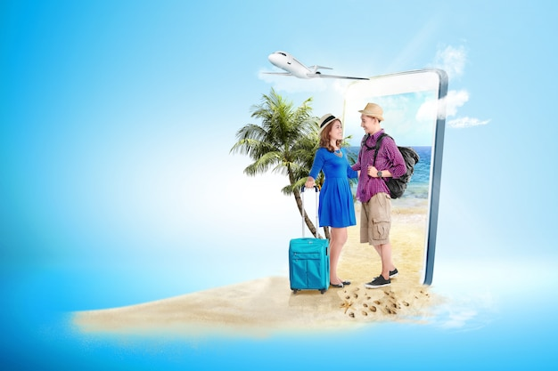 Asian couple with suitcase bag and backpack standing on the beach