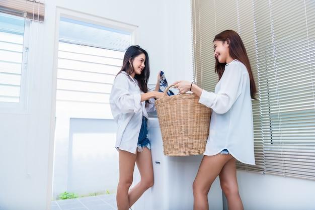 洗濯機の前で家事や家事をしているアジアのカップルの女性