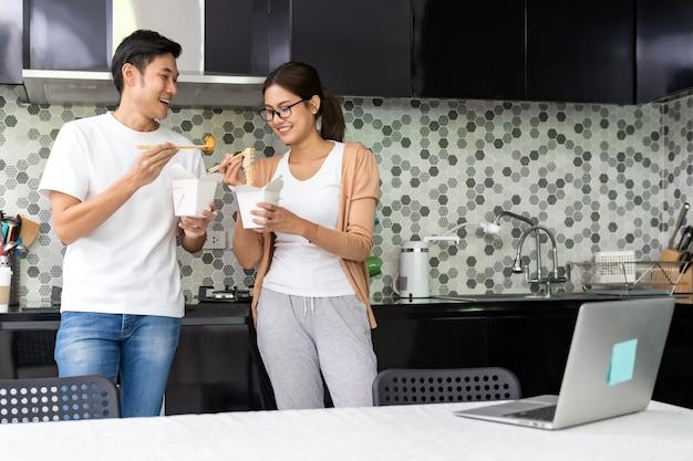 アジアのカップルが中国人を食べる作業はテーブルの上のノートパソコンとキッチンで食べ物を取り出す