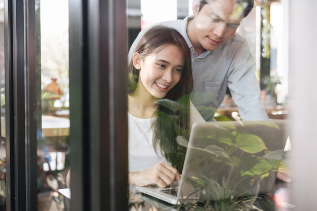 Asian couple working with laptop in coffee shop cafe