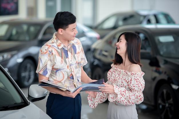 Азиатские пары с удовольствием покупают новую машину в автосалоне. концепция покупки автомобиля и концепция успеха