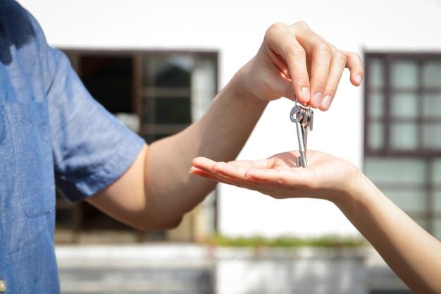 アジアのカップルは一緒に滞在するために家を買う。男性は女性に家の鍵を与えます。幸せな家族を始めるというコンセプト