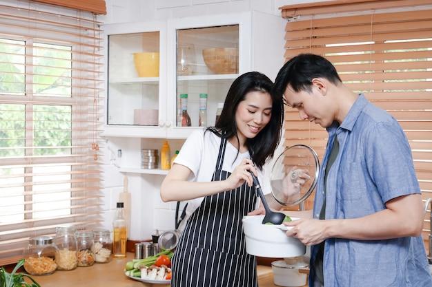 아시아 커플은 그들의 가정 부엌에서 함께 요리를 즐긴다 프리미엄 사진