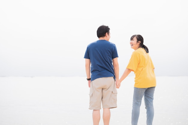 海の背景のプライベートビーチで手をつないでアジアのカップル