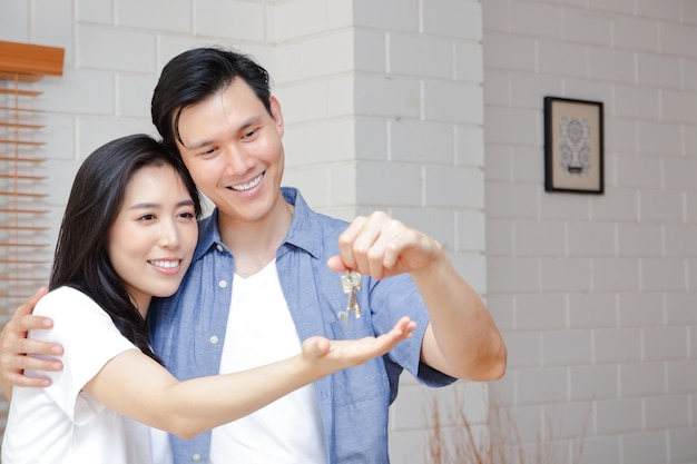 新しい家でお互いをハグするアジアのカップル男性は女性に家の鍵を渡します。幸せな家族を始めるのコンセプト。コピースペース