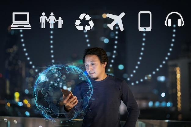 Азиатский креативный фрилансер, использующий смартфон с частицами земли для работы с различными