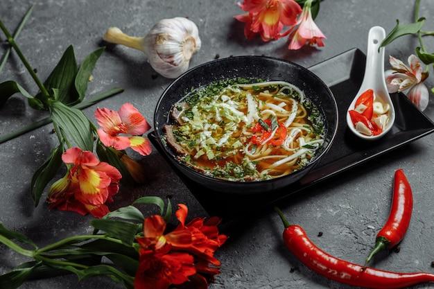 アジア料理、暗い背景に黒い皿に牛肉のスープfo。スパイシービーフスープ、ビーフテンダーロイン、うどん、チリペーストのスープfo