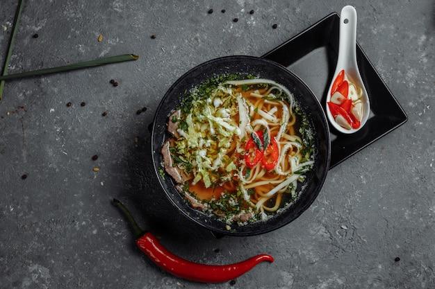 아시아 요리, 쇠고기 수프 fo 어두운 테이블에 검은 접시에. 매운 쇠고기 국물을 곁들인 수프 fo