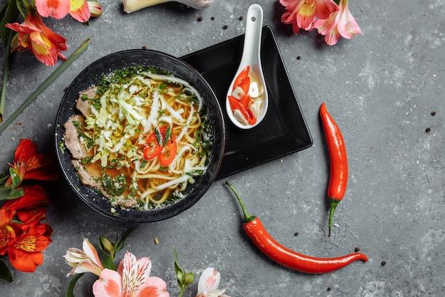 Азиатская кухня, говяжий суп fo в черной тарелке на темноте.