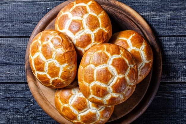 Asian cuisine: chinese pineapple buns - soft and fluffy milk buns served on a round cutting board on a dark wooden background, top view, close-up