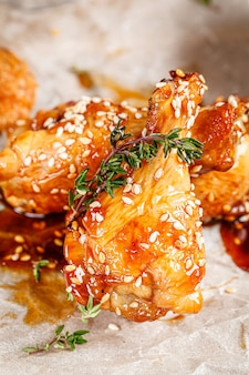 Asian cuisine glazed fried chicken legs with spicy chili sauce and sesame seeds