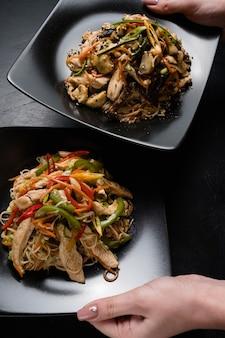 Азиатская кухня. здоровый ужин. сбалансированное питание. женщина, подающая куриный гриб и овощной салат на черных тарелках