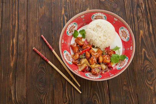 アジア料理、ピーマン、タマネギ、パイナップルを添えた甘酸っぱい揚げ豚肉のチャンク、古い木製のテーブルの上に、ご飯と箸を添えた伝統的な赤いプレート