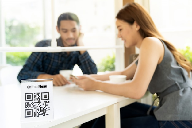 Азиатский клиент ищет онлайн меню после сканирования qr-кода. клиент сидел на социальном дистанционном столе для нового нормального образа жизни в ресторане после коронавирусной болезни.