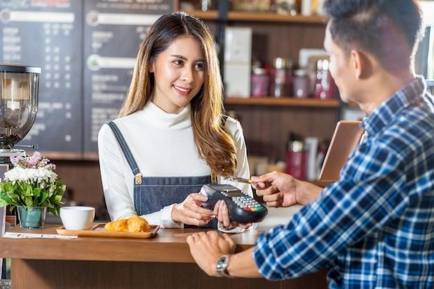비접촉 nfs 기술을 통해 신용 카드로 아시아 바리스타에게 결제하는 아시아 고객