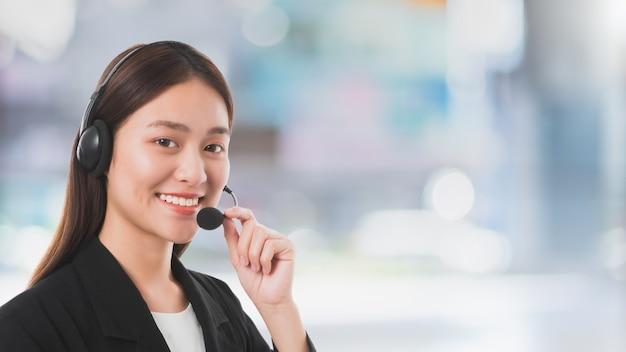 콜 센터 연락처 사무실 공간 배경에서 작업하는 마이크 헤드셋을 가진 아시아 고객 서비스 운영자 여성. 아름답고 웃는 얼굴. 텔레마케팅 에이전트 작업 개념입니다.