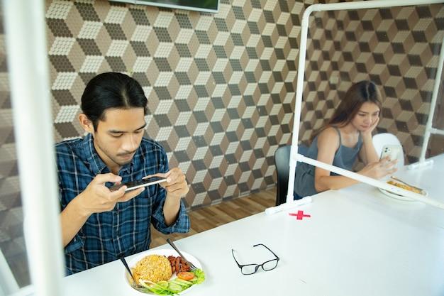 スマートフォンを使用して、社会的距離の概念のための新しい通常のランチフードを撮影するためにスマートフォンを使用しているアジアの顧客。食事をする前に記録画像のために携帯電話を持っているタイ人男性。