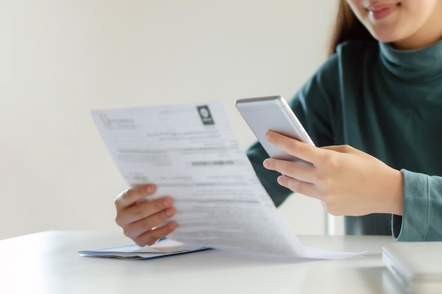 Asian customer woman using mobile smart phone for scan and payment online with family budget cost bill on desk at home office, plan money cost saving, investment, business finance, expenses concept