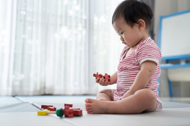 Asian cute baby sitting and playing a small toy on soft mat at home.