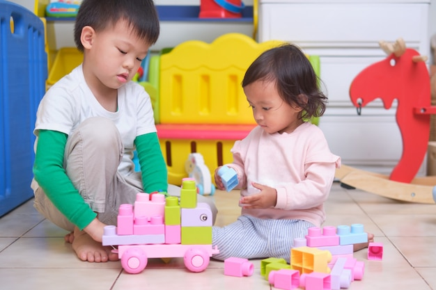 Asian cute big brother and little sister having fun playing with toy blocks in play room at home, educational toys for young kid, bonding of sibling, learn through play