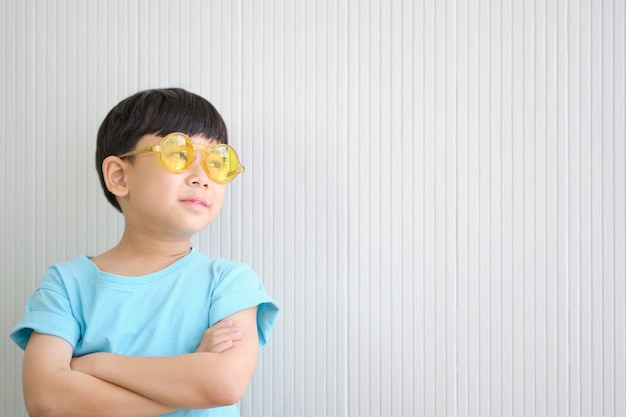 Asian cute boy is daydreaming while wearing yellow sunglass