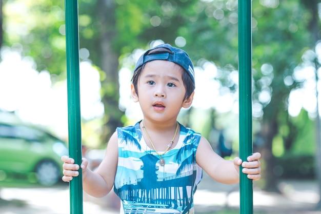 アジアのかわいい男の子が遊び場で遊んでいます。
