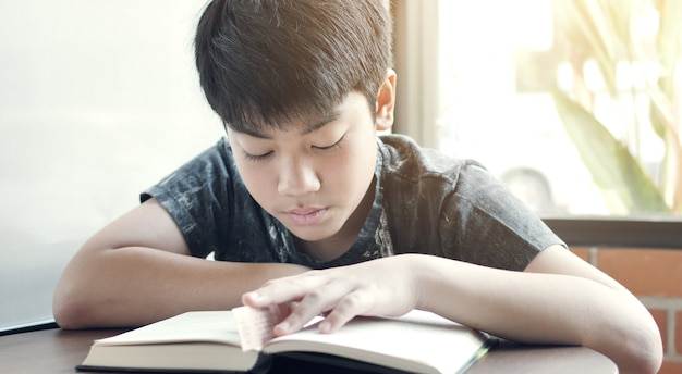 Asian cute boy read books in the cafe.