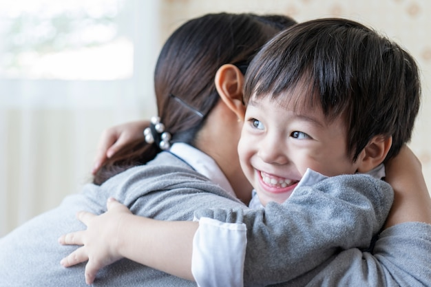 Asian cute boy smiling with happily and hugging with mother at home, family concept