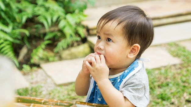 Asian cute child eating a snack in a garden.