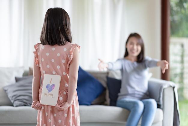 Азиатская милая девушка скрывает открытку ручной работы со словом я люблю маму, чтобы удивить ее мать дома