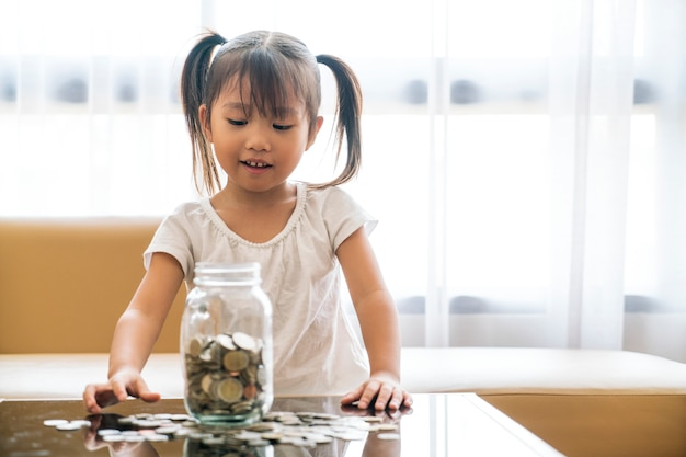 Asian cute girl saving money putting coins into glass bank