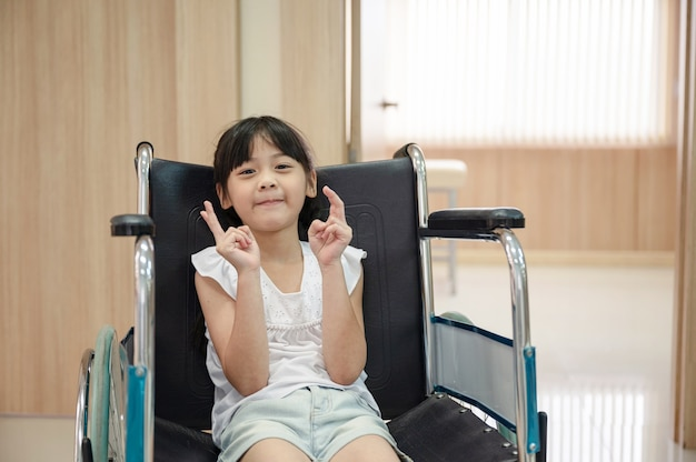 Asian cute girl smiling and raised finger in wheelchair at hospital