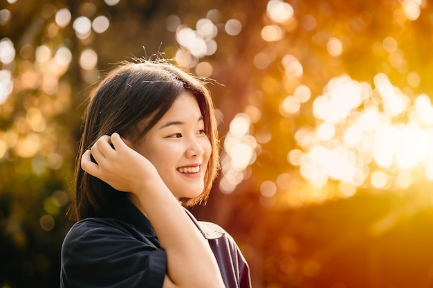 Asian cute girl teen innocent shy smiling happiness moment with nature sunshine beautiful background