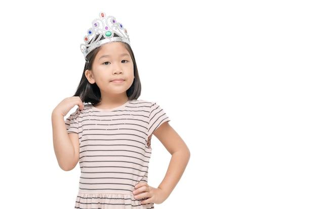 Азиатская милая девушка в короне и коричневом платье, изолированном на белом.