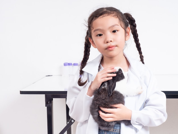 Asian cute girl wearing medical uniform and holding a baby black and white rabbit. little cute girl 5-6 years old role playing veterinarian doctor occupation.