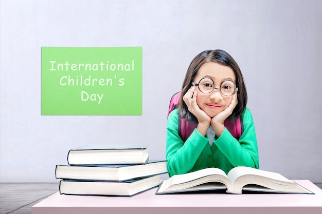 Asian cute girl with glasses and backpack sitting and read the book with a gray wall