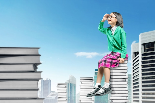 Asian cute girl with glasses sitting on the pile of books and looking forward