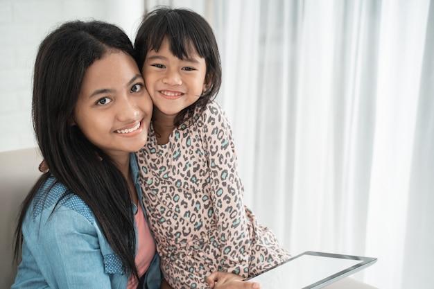 Азиатские милые счастливые сестры улыбаются